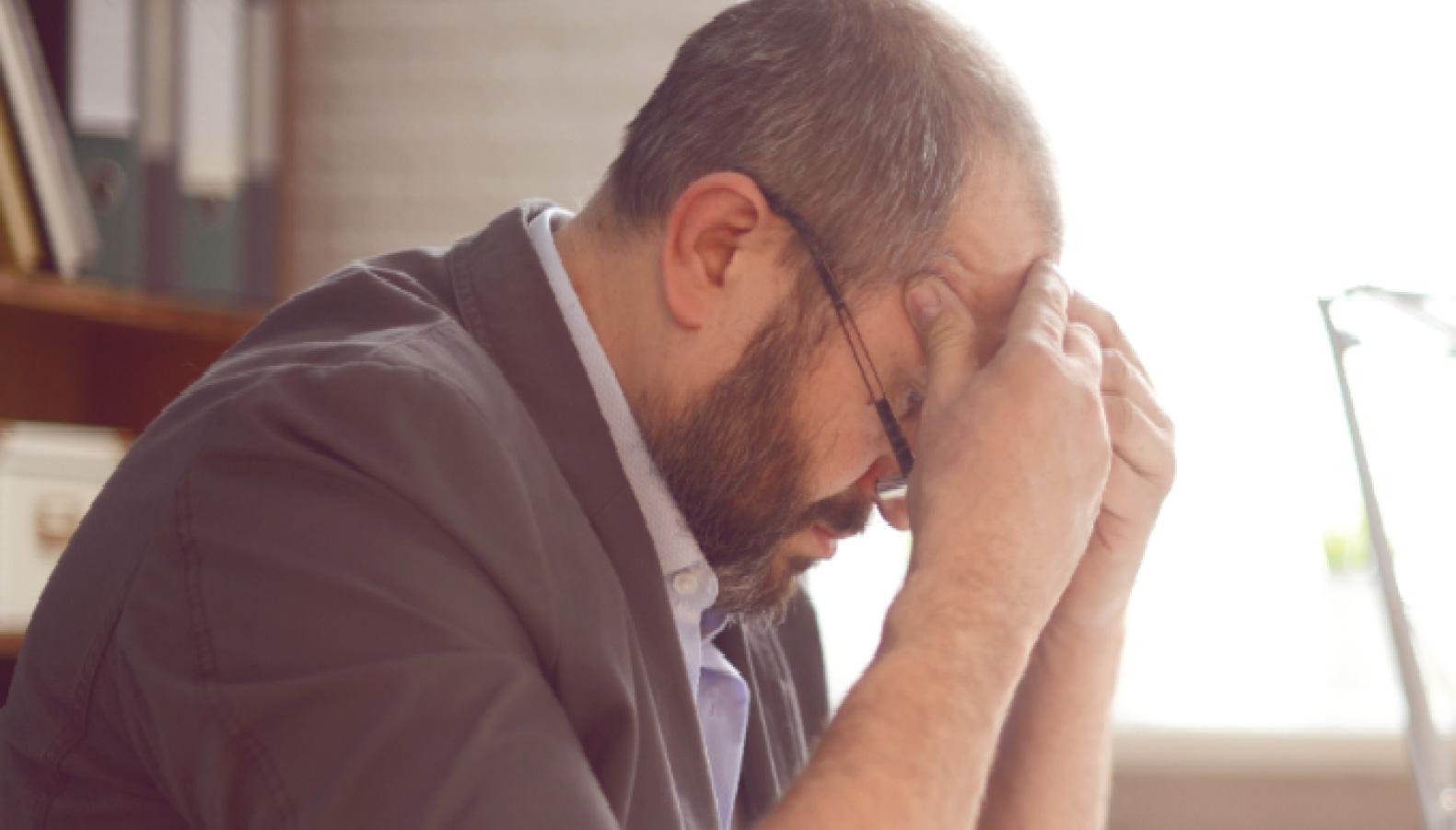Man med glasögon som lutar över ett bord med ett stressat uttryck