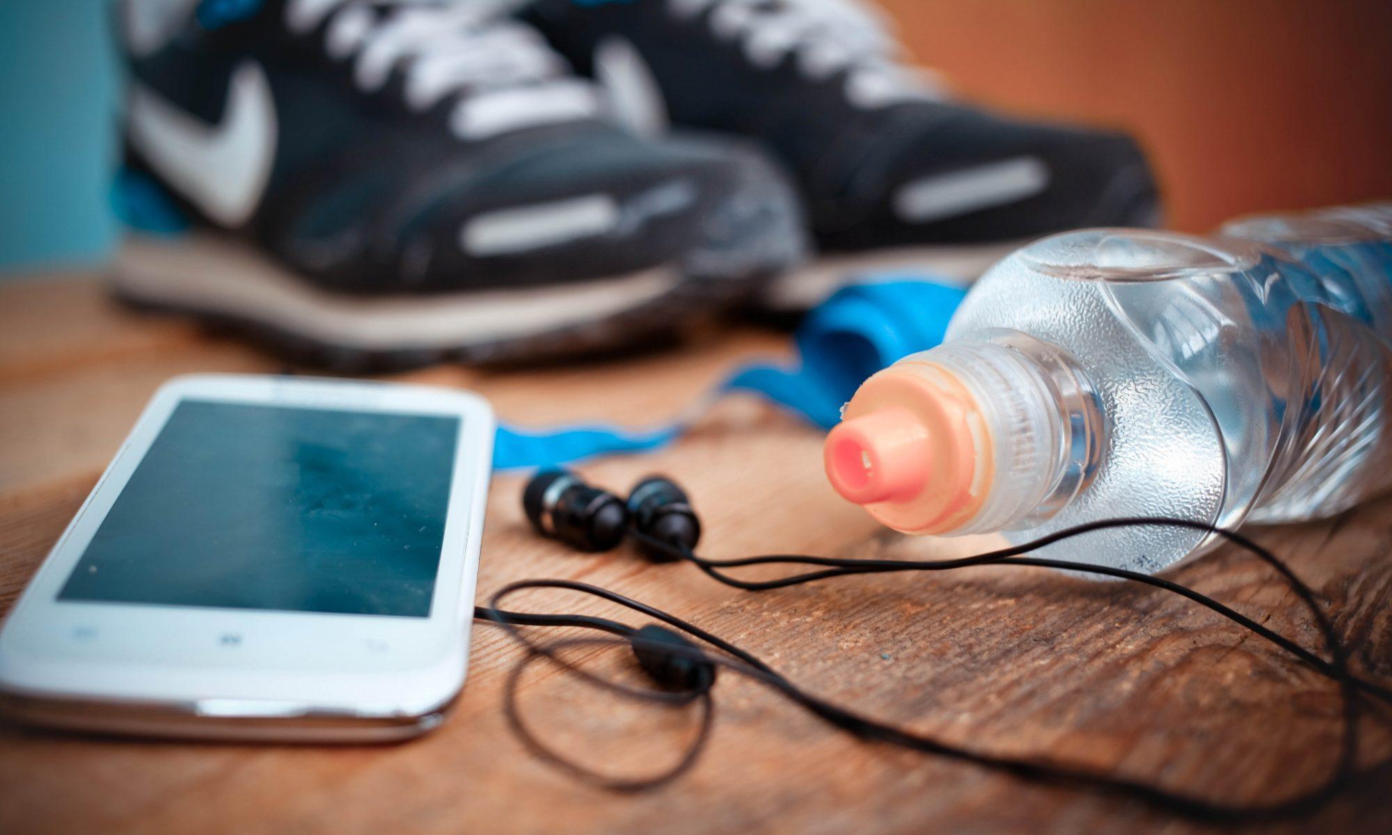 Svarta sportskor, vattenflaska och en mobil ligger på en träbänk