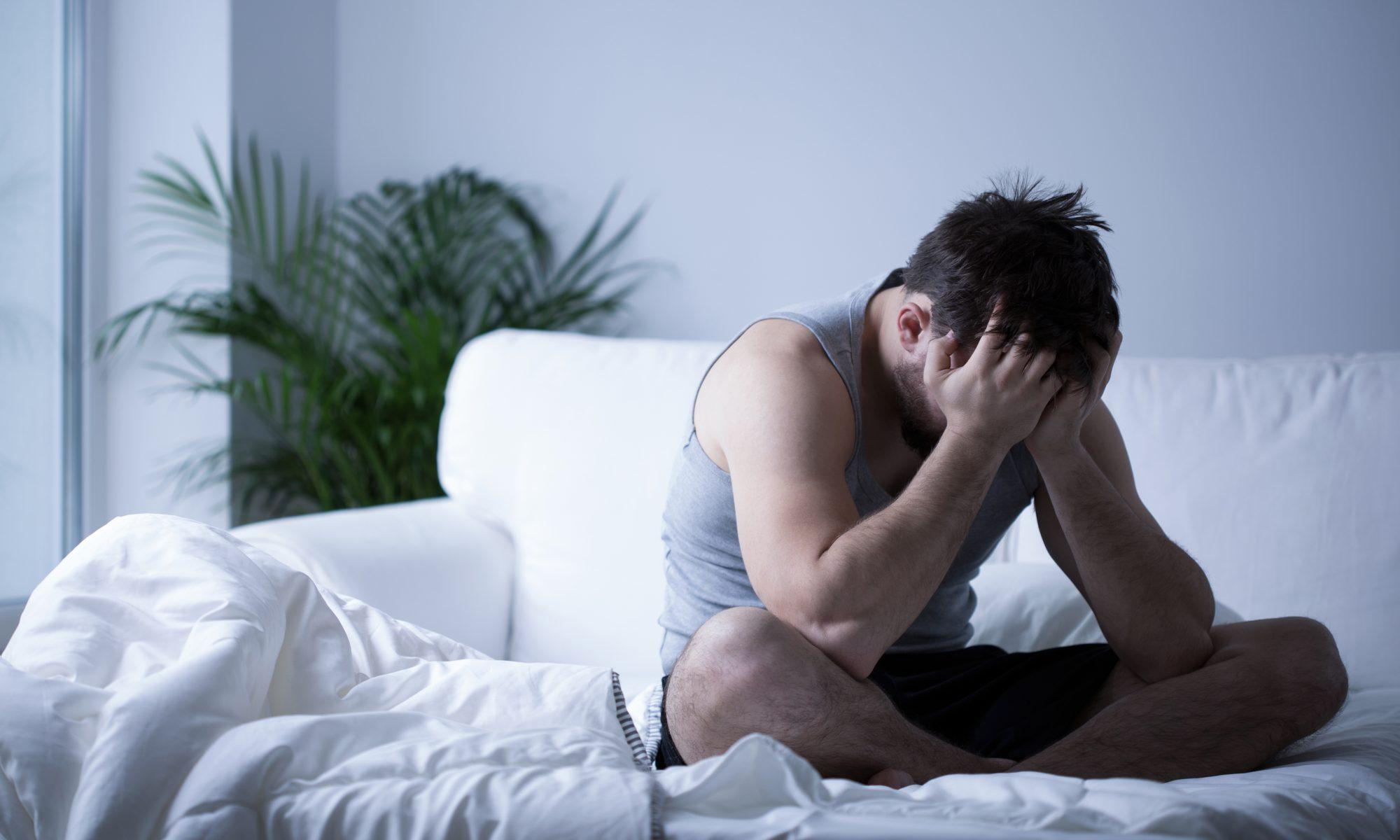 Man sittandes på en bäddsoffa med huvudet vilandes i händerna på grund av för lite sömn