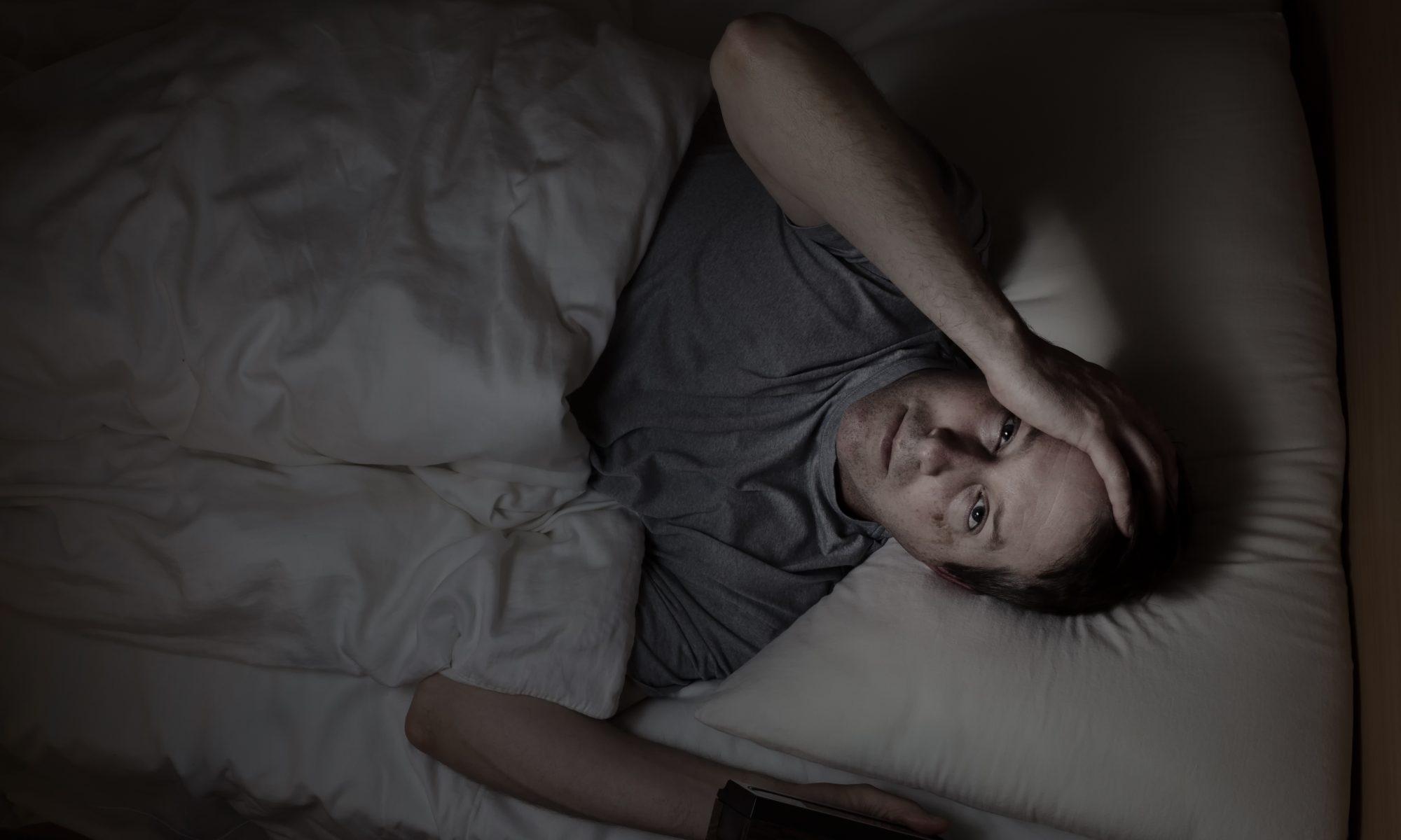Man med grå t-shirt liggandes vaken i sängen på grund av stress