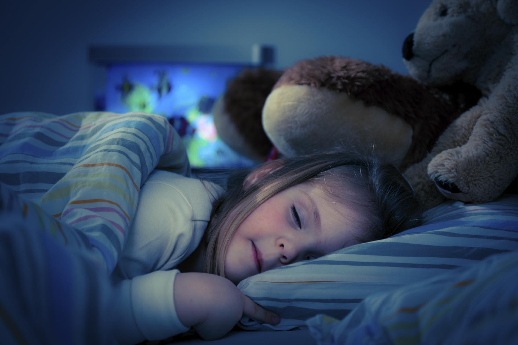 En liten flicka med långt hår sovandes i sin säng med gosedjur