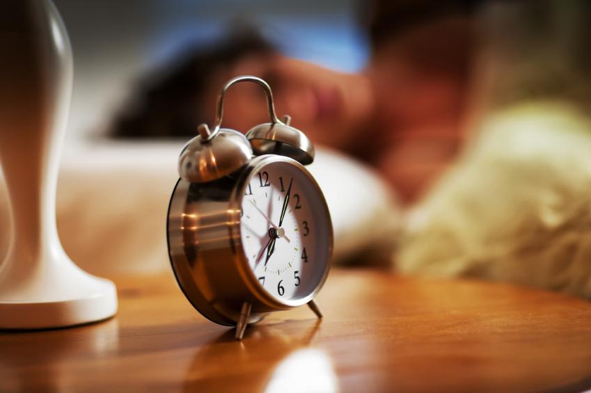Väckarklocka ståendes brevid en säng på ett träbord